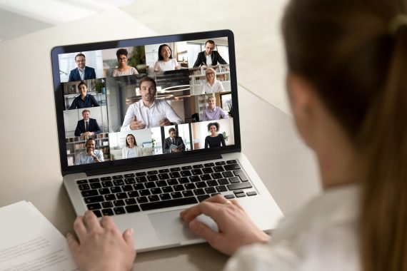 Female employee engaged in webcam conference with diverse colleagues